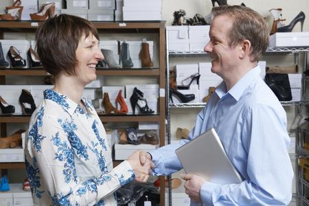 tienda zapatos: El hombre de negocios que sacuden las manos con el minorista tienda de zapatos Foto de archivo
