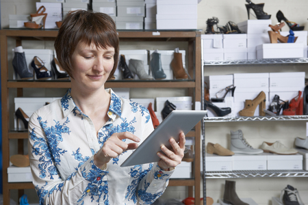 40s: Owner Of Online Shoe Business Using Digital Tablet
