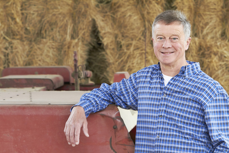 bailer: Farmer Standing In Front Of Bales And Old Farm Equipment