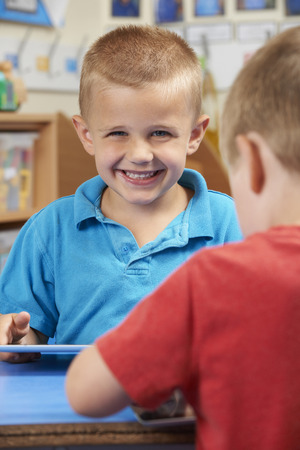age 5: Elementary School Pupil Using Digital Tablet In Classroom