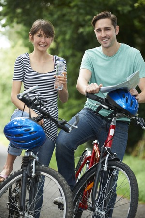 whilst: Young Couple Having Break Whilst On Country Cycle Ride