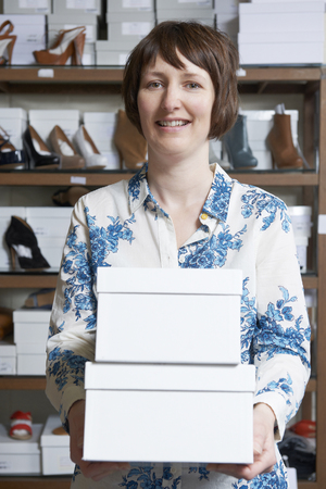 shoe boxes: Female Owner Of Shoe Store Carrying Boxes
