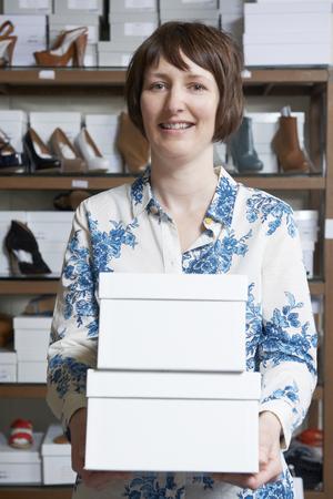 tienda zapatos: Propietario de sexo femenino de zapato tienda Llevar las cajas