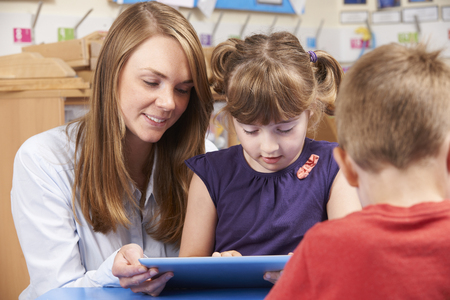 4 5 year old: Teacher Helping Elementary School Pupil Use Digital Tablet Stock Photo