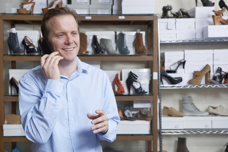 shoe store: Male Owner Of Shoe Store On Phone Stock Photo