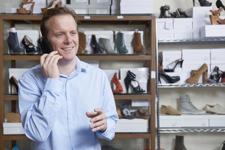 tienda de zapatos: Propietario de sexo masculino de zapato tienda en el teléfono