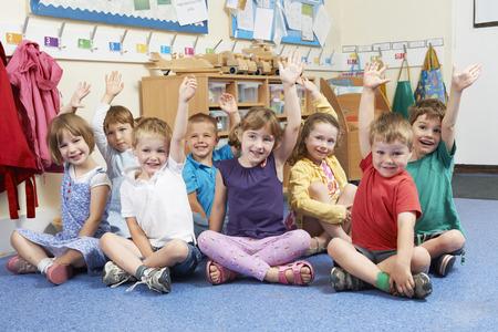 niños sentados: Grupo de alumnos de escuelas primarias que pone las manos en la clase