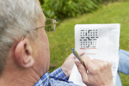 crossword puzzle: Senior Man Doing Crossword Puzzle In Garden