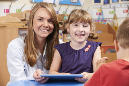 4 5 year old: Teacher Helping Elementary Scool Pupil To Use Digital Tablet Stock Photo