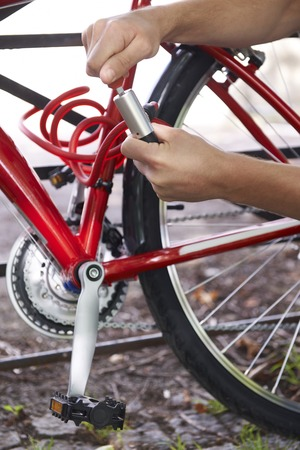 securing: Cyclist Securing Bike With Lock