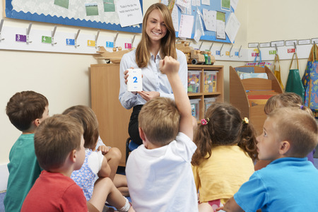 enthusiastic: Teacher Using Number Flash Cards To Teach Maths Stock Photo