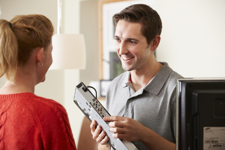 service man: Engineer Giving Advice On Installing Digital TV Equipment Stock Photo
