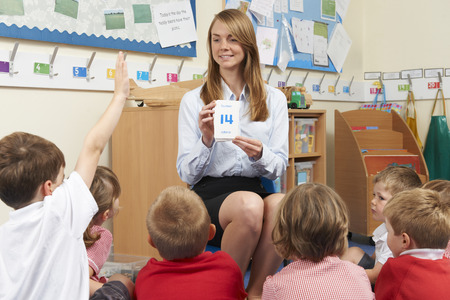 teaching and learning: Teacher Using Number Flash Cards To Teach Maths Stock Photo