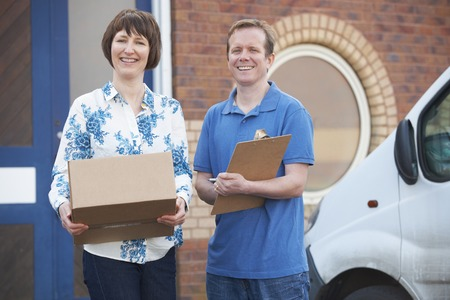 courier: Courier Delivering Package To Client Stock Photo