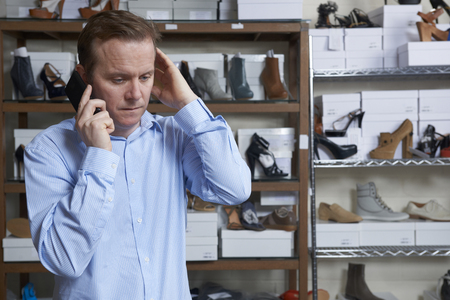 Online Business: Worried Owner Of Shore Store On Phone Stock Photo