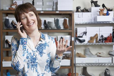 tienda de zapatos: Propietario de la tienda de zapato en el teléfono Foto de archivo