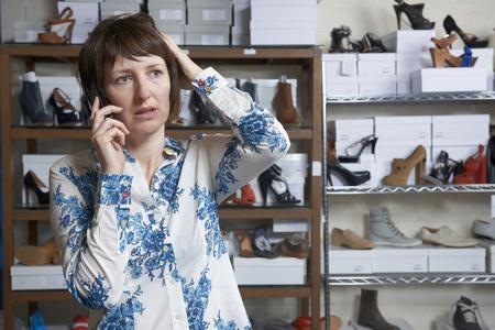 tienda de zapatos: Propietario preocupado de zapato tienda en el teléfono