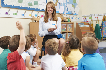 4 5 year old: Teacher Using Flash Cards To Teach Maths To Elementary Class