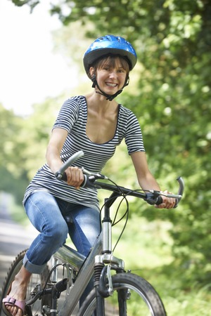 road cycling: Young Woman Cycling On Country Road Stock Photo