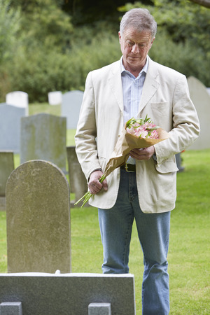 grave: Man Laying Flowers on Grave