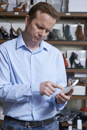 tienda de zapatos: Propietario preocupado de zapato tienda Con la calculadora Foto de archivo