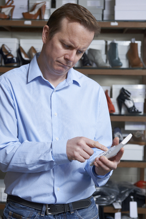 shoe store: Worried Owner Of Shoe Store With Calculator