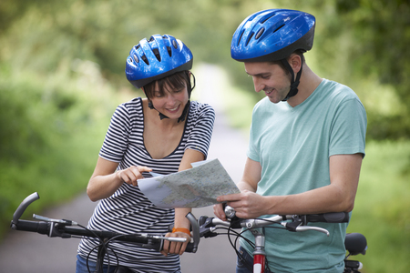whilst: Young Couple Looking At Map Whilst On Cycle Ride