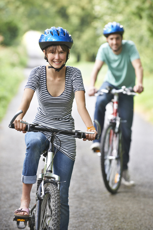 road cycling: Young Couple Cycling Along Country Road Stock Photo