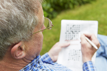 Senior Man Doing Crossword Puzzle In Garden Banque d'images - 49601444