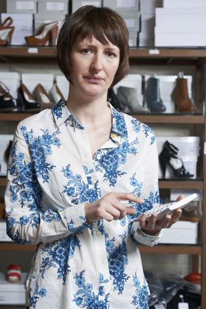 tienda zapatos: Propietario preocupado de zapato tienda Con la calculadora Foto de archivo