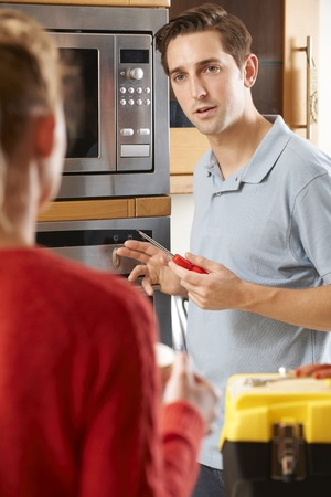 mid thirties: Engineer Giving Woman Advice On Kitchen Repair Stock Photo