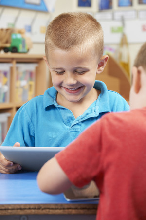 4 5 year old: Elementary School Pupil Using Digital Tablet In Classroom