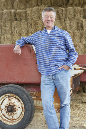 bailer: Farmer Standing In Front Of Straw Bales And Old Farm Equipment