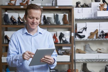 tienda de ropa: Negocios que se ejecuta negocio de zapatos en línea con la tableta digital Foto de archivo