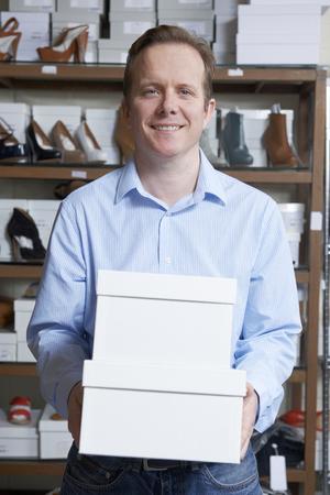 tienda de zapatos: Propietario de sexo masculino de zapato tienda Llevar las cajas Foto de archivo