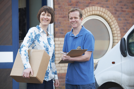 courier: Courier Delivering Package To Customer Stock Photo