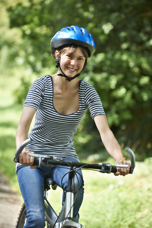 road cycling: Young Woman Cycling Along Country Road