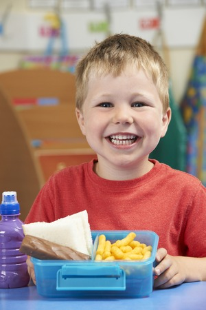 the pupil: Elementary School Pupil With Unhealthy Lunch Box Stock Photo