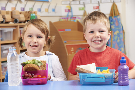lunch meal: Elementary School Pupils With Healthy And Unhealthy Lunch Boxes