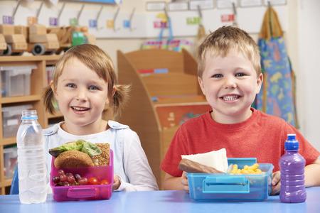 escuela primaria: Los alumnos escuela primaria con el sano y fiambreras poco saludables