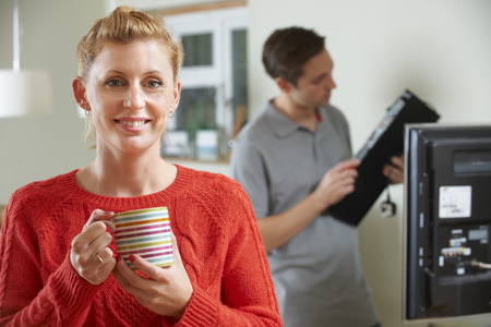 whilst: Woman Holding Mug Whilst Engineer Installs TV Equipment
