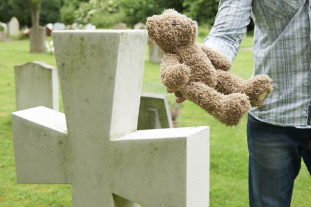 bereavement: Father Placing Teddy Bear On Childs Grave In Cemetery Stock Photo