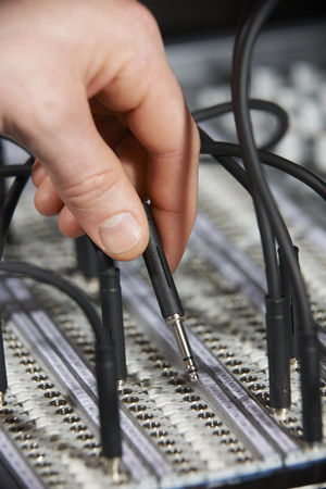 plugging: Engineer Plugging Cable Into Patch Panel