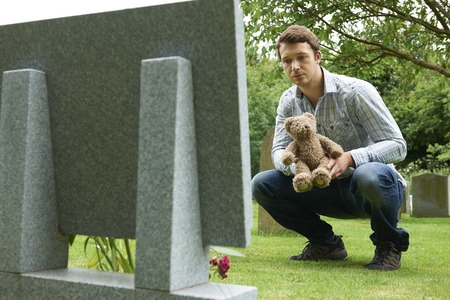 graves: Father Placing Teddy Bear On Childs Grave In Cemetery Stock Photo