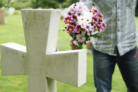 tombstones: Man Laying Flowers On Grave