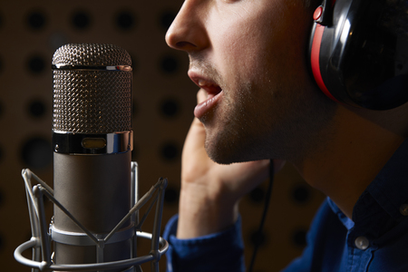 cantando: Vocalista de sexo masculino que canta en el micrófono para grabaciones en estudio Foto de archivo