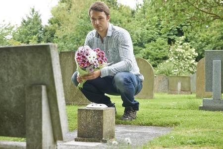 Hombre que coloca las flores de la lápida mortuoria en cementerio Foto de archivo