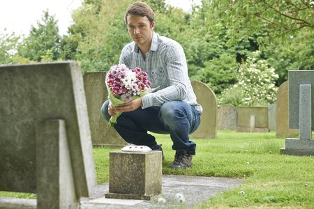 cemetery: Man Placing Flowers By Headstone In Cemetery