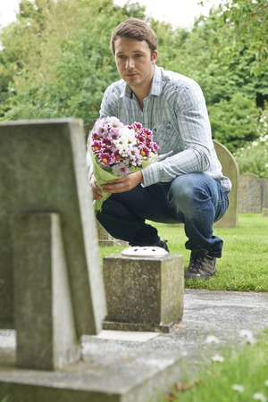 graves: Man Laying Flowers At Grave