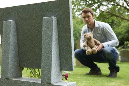 death: Father Placing Teddy Bear On Childs Grave In Cemetery Stock Photo